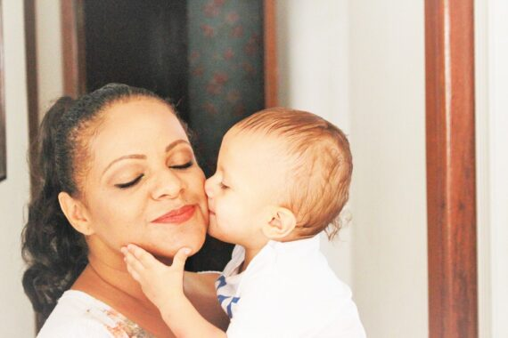 baby kissing mum on cheek