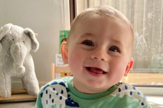 laughing baby with toys in background