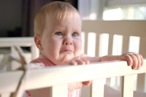 baby standing and crying in cot